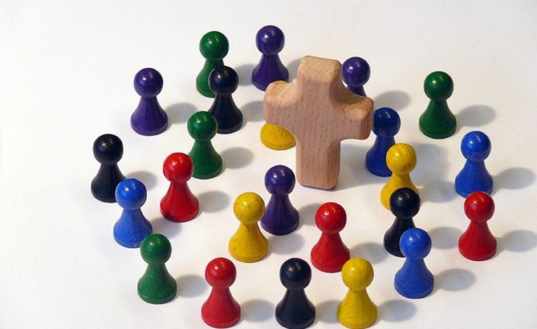 Bunte Holzfiguren um Kreuz versammelt